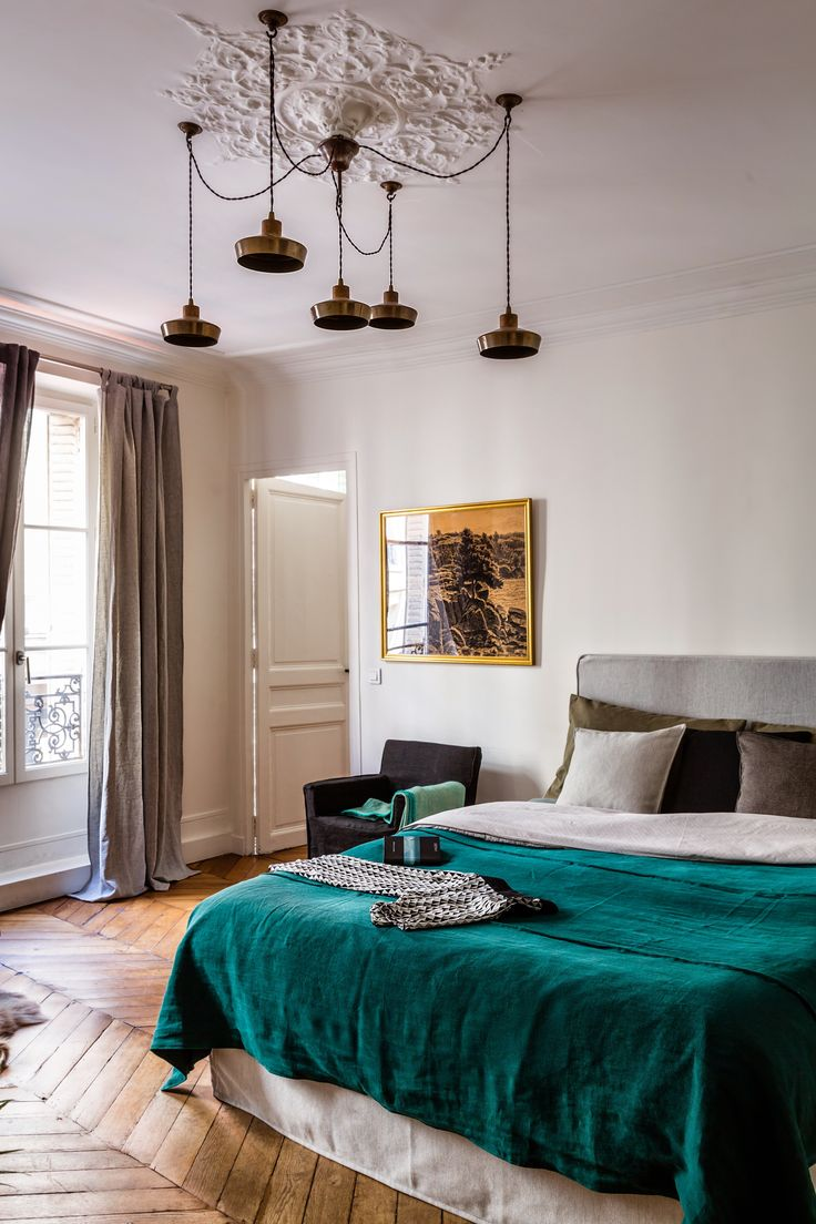 Elegant Parisian style bedroom with glamorous ceiling medallion and wooden chevron floors | floor length curtains | modern bedroom styling with a dark green linen bedspread | Bemz bedspread in Ivy Brera Lino linen