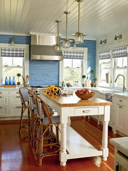 Honed stone countertops lend polished 1930's charm to this coastal kitchen. Blue recycled glass backsplash in a running bond pattern not only makes a statement but is easy to clean and extremely durable. (Photo: Tria Giovan) Love the ceiling