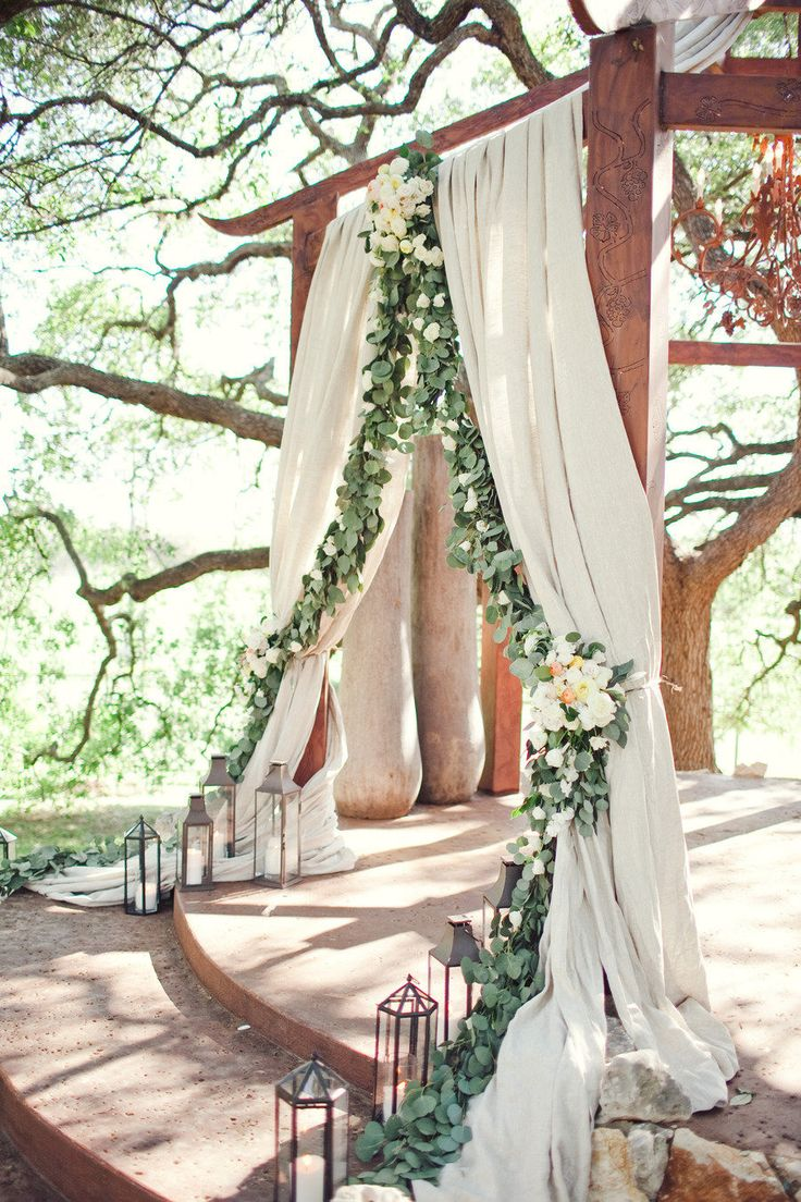 """The ceremony site will feature a garland of eucalyptus and bay laurel swagging back with the curve of the """"taupe"""" colored fabric curtains. Clusters of white hydrangeas, Juliet garden roses, ivory spray roses and blush spray roses will be in the top, middle and on the sides of the design."""