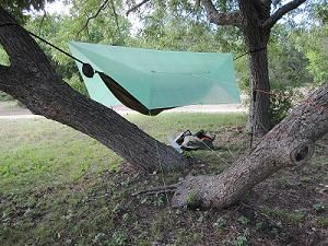 Hammock Tarp Weight:  7.0 ounces  Dimensions: Ridge Line: 11 feet long (3.35 meters) Width:  8.5 feet wide (2.6 meters) Base Line: 7 feet long (2.1 meters)  Tie out loops: 8 Perimeter tie outs, plus 2 additional tie outs on each wall of the tarp. (12 tie outs total).   Stuff sack included.