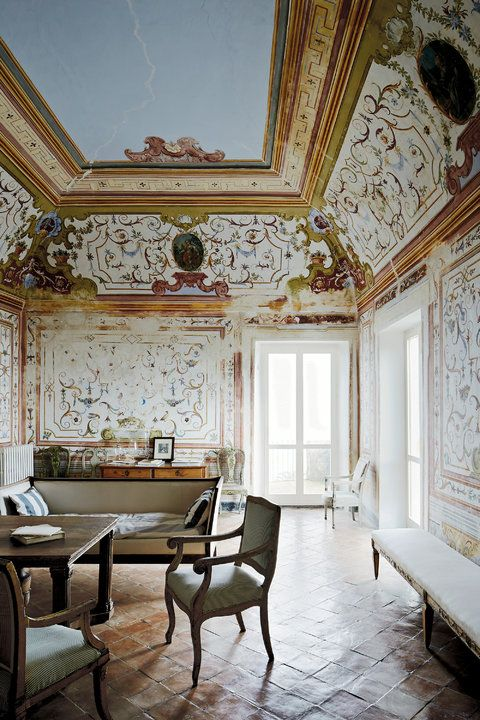 The grand sitting room of the main house that dates from A.D. 1000, on the property of Nicola Del Roscio, Cy Twombly's archivist and close companion, in Gaeta, Italy, with 18th-century frescoes thought to be by the artist Sebastiano Conca, a sofa from Andy Warhol's home in Paris and terra-cotta tiles on the floor, handmade in a nearby village.