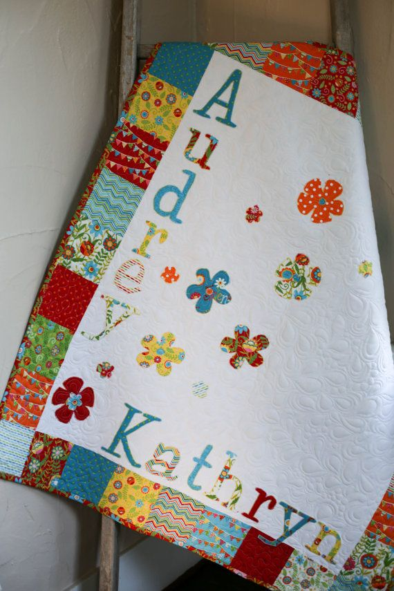 Create a homey vibrancy in your baby's nursery with this irresistible floral baby quilt from The Quirky Quiltr. Artistically designed from A to Z, it features a solid white fabric that is embellished with colorful print fabric patched all around the border. A series of fabric flowers blossom just above your child's appliqued name. The back features a floral fabric and red print edging finishes off the look with adorability. Whether taking a stroll in the park or fitting a nap into a busy day…