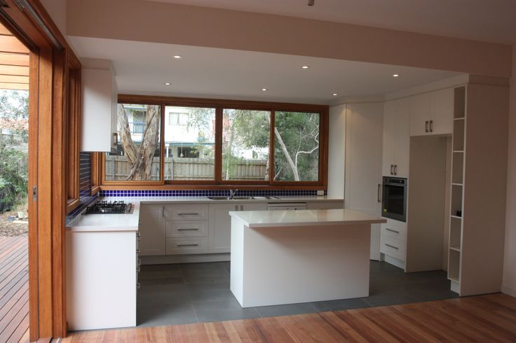 View of the new kitchen - simple clean lines, with a great dark blue feature tile to the splashback
