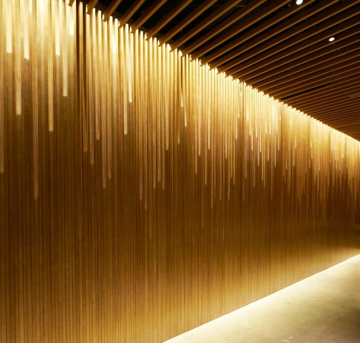 The locale's specialty is expressed with a spatial gesture of a flowing waterfall. A ceiling of staggered struts drips into a stream of stick LED…