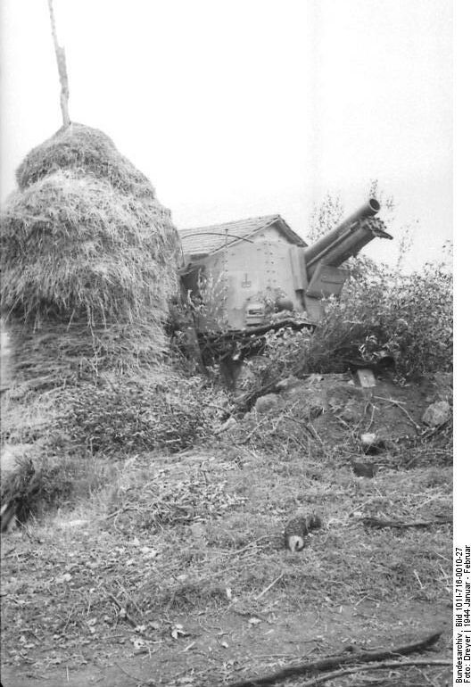 """Self-propelled artillery """"Grille"""" nicknamed """"Fire Devil"""" in a firing position in Italy in January 1944. The crew has chosen a position next to a haystack and heavily camouflaged the vehicle with foliage.The """"Grille"""" (""""Cricket"""") was a German self-propelled, heavy artillery vehicle armed with the 15 cm sIG 33 infantry gun in a fixed superstructure. The official German designation was 15 cm schweres Infanteriegeschütz 33 (Sf) auf Panzerkampfwagen 38(t) (Sd.Kfz. 138/1)."""