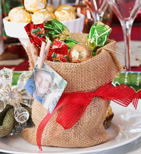 How to make santa sacks: Make mini Santa sacks that double as place markers and goodie bags. Instead of name cards, use tiny pegs to clip a photo of each guest to ea...