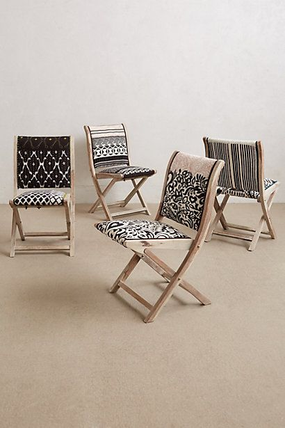 Folding chairs with pastel embroidery.