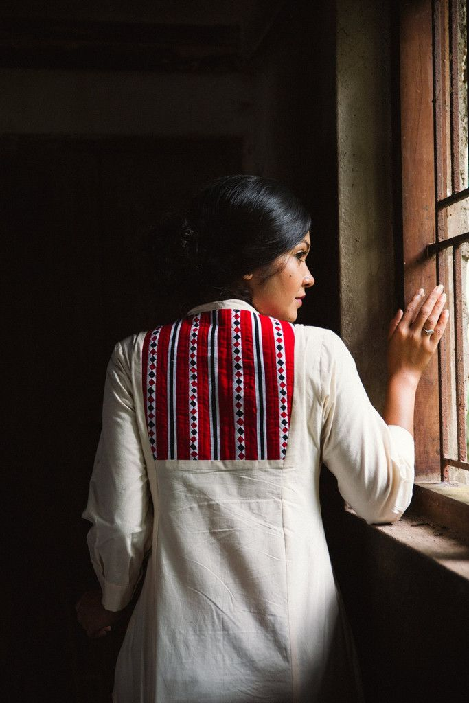 A crisp off white button down jacket with detail on the bodice and back. The appliqué detail on the back in red and black have been hand made by the Theyyam ...