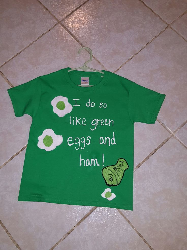 """This shirt took some time but I really like how it turned out. I messed up by the """"ham"""" word so becareful with that crazy fabric pen. I bought everything at Hobby Lobby. One trip and you get to use a coupon! Items: Shirt ($2.50) and white, lime green felt fabric (.33) and the white fabric pen (1.29) and a black permanent marker. Make your eggs shape and ham and outline the ham w/ the marker. I hot glued black yarn around the ham to make it stand out. Oh and I sewed the eggs & ham on the…"""