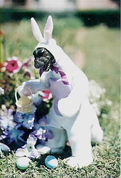 A plastic dinosaur in a bunny suit.