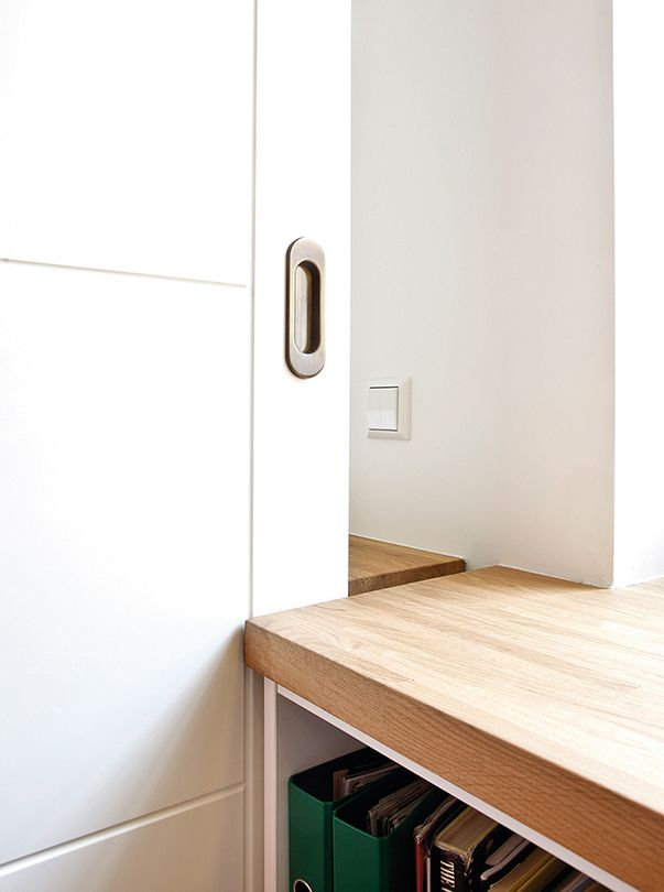 Между спальней и гостиной — широкая раздвижная дверь со встроенными ручками. Закрываясь, она входит в щель между стеллажами, а днём её задвигают в «пенал» за стеной спальни, чтобы в квартиру попадало как можно больше естественного света — практичное интерьерное решение для маленькой квартиры.  © 4living.ru