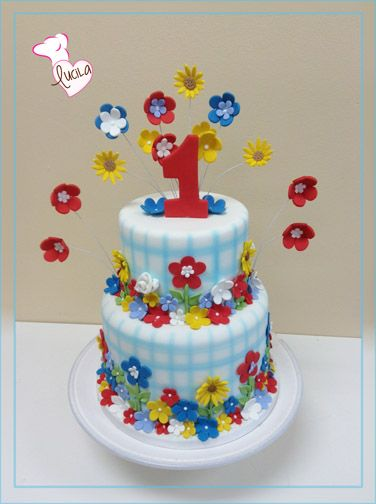 Multicolor cake with flowers and fondant number on top.