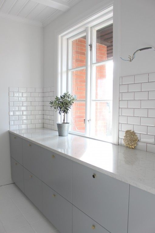 Grey cupboards subway tiles and white floor in this minimal kitchen