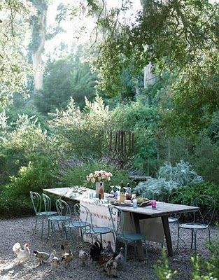 Secret garden setting with rustic table and chairs.