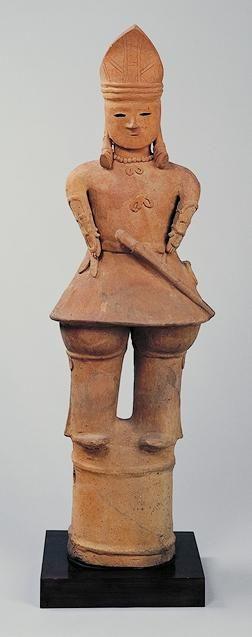 埴輪 天冠をつけた男子   天冠をつけた盛装の男子埴輪で、下半身が省略されがちな人物埴輪の中では、特に出来のよいものの一つである。古代人らしい無垢な顔立ちで、箆一筋で表された小さい口と、太く大きく切られた生き生きとした目とは、まったく不釣り合いであるにもかかわらず、不自然さはなく、高く大きい鼻で整えられ、不思議なほどの均衡を保っている。紐で束ねた太いみずらを肩先まで垂らし、頸玉を飾り、三角形の天冠をつけており、謹厳な貴人に見える。籠手をつけた、長い筒袖の盤領の上衣は、重ねが表されていないが、上下二つの紐結びで合わせた左衽で、裾は大きく広がっている。下には、襞折りのある太い袴をはき、膝上あたりを紐で結んでいる。円頭の太刀を差し、鞆を腰に吊るしている。群馬県伊勢崎市波志江町出土。   古墳時代(6世紀~7世紀)