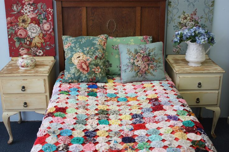 floral embroidered pillows, crocheted blanket, bedside tables, oh such lovely goodness.