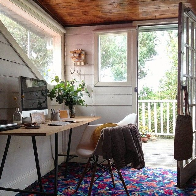 White shiplap wall, rustic wooden desk, geometric windows, mid century modern chair, workshop retreat