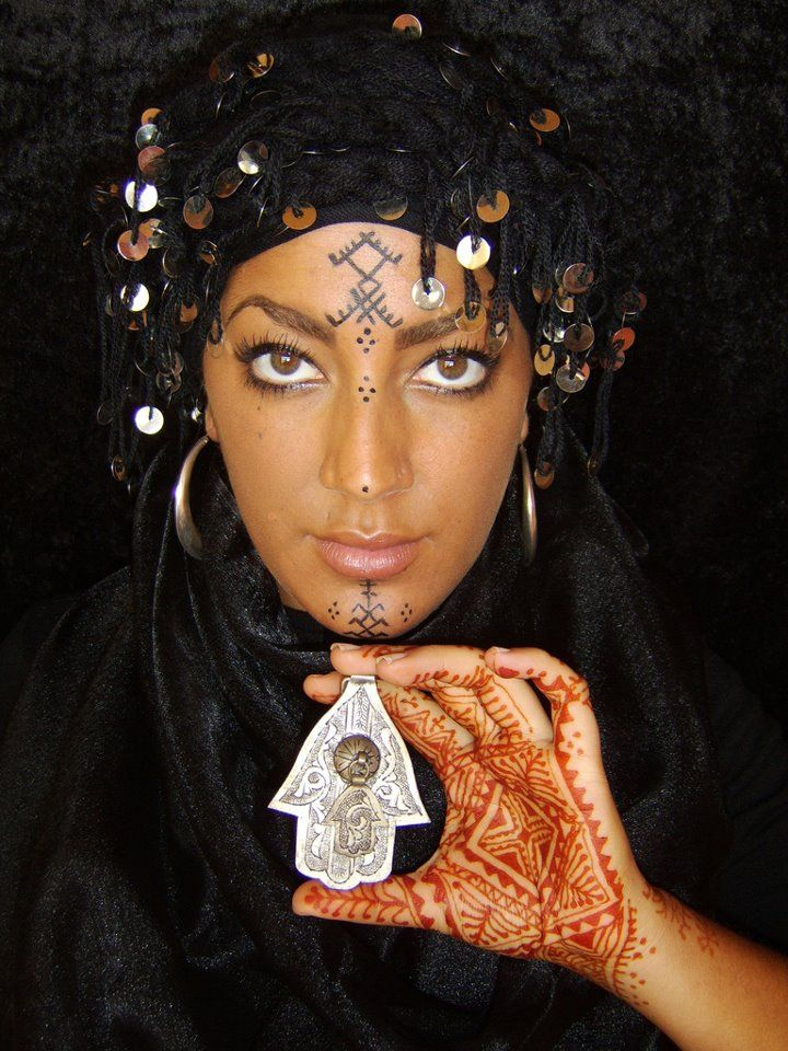 Mozunas. North African girl with tribal facial tattoos henna'd hands and a hamsa amulet