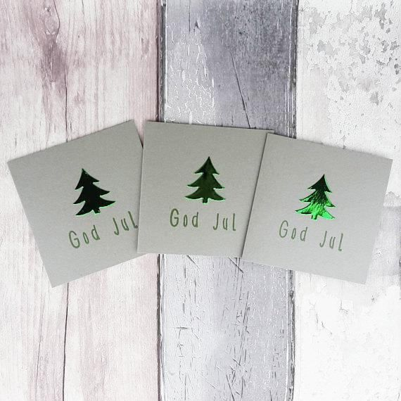These mini handmade silver Christmas cards are 4 inches wide and 4 inches tall and feature a Christmas tree (Xmas tree) embellishment in either pearlescent or foiled card with a selection of colours and messages, including: God Jul, for you to personalise your cards.  The message on the front of the card is hand stamped with same colour ink to match the Christmas tree embellishment.  These cards are available in packs of 6 or 12, with an additional saving on the 12 packs.  PERSONALISING YOUR…