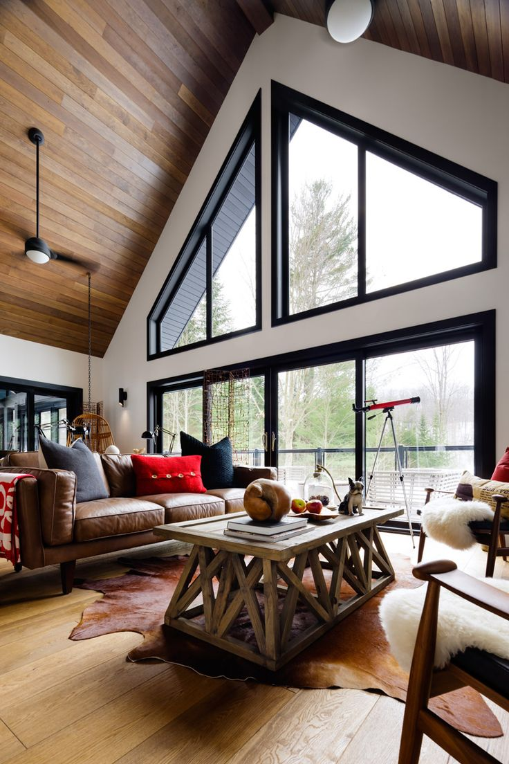Such incredible floor to ceiling windows. Love the modern take on this cottage. The wood and brown leather really give a homely feel to the red, black and white colour scheme! Before and After: A Designer Cottage in Haliburton County, Ontario | Design*Sponge