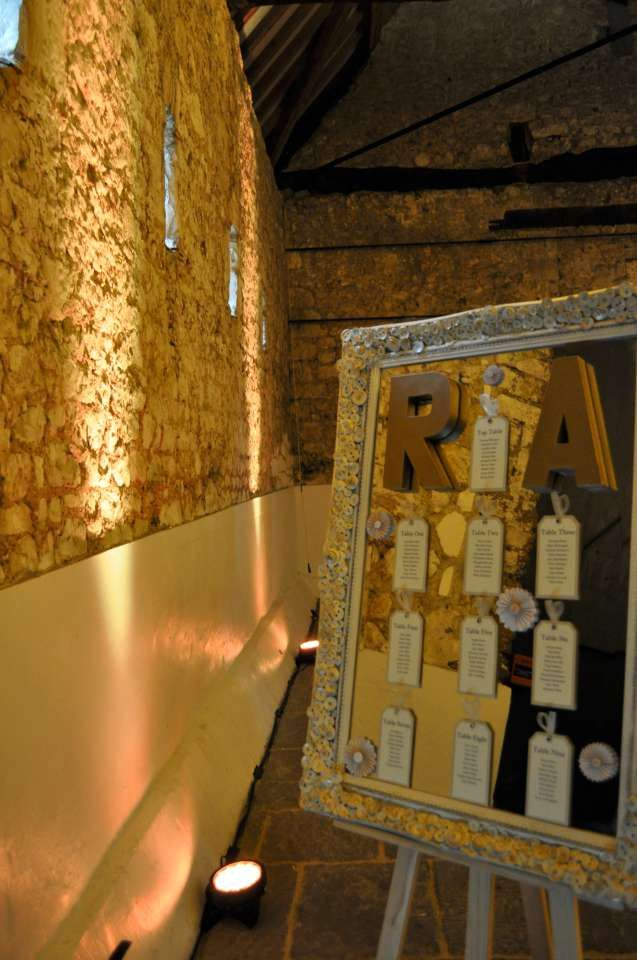 Gold uplighting for weddings, highlighting beautiful stone walls at the Monks Barn