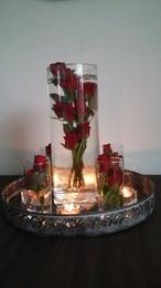 Zet roosjes in een vaas. Vul het met water parels zo blijven de roosjes ophyn plaats. Vul aan met water. Leuk op dienblad met kaarsjes en glazen met roosjes.