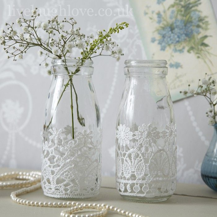 This is a pair of miniature glass milk bottles which both come with pretty white lace trim both with a different pattern. What could be prettier than these bottles filled with flowers from your garden.