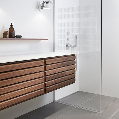 Bathroom with an elegant glass shower screen - no visible screws or fittings. Shower with linear floor drain. Elegant grating and frame in brushed stainless steel. Unidrain® GlassLine & ClassicLine