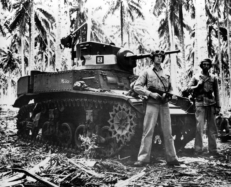 Description of  Nov. 4, 1942: Two alert U.S. Marines stand beside their small tank on Guadalcanal in the Solomon Islands during World War II. The military tank was used against the Japanese in the battle of the Tenaru River during the early stages of fighting. (AP Photo)