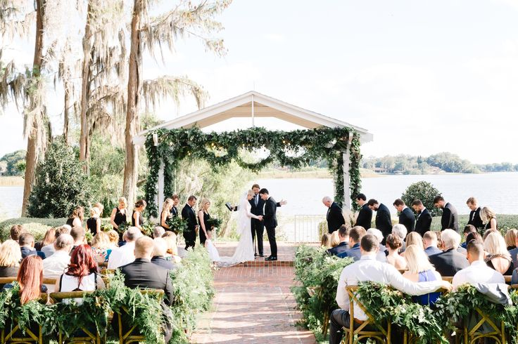 this florida lakeside estate home's gazebo is dressed for the wedding ceremony with lush garlands of fern, lemon leaf and eucalyptus and strings of edison bulbs in the rafters. the aisle is lined with lush garlands and guests are seated in french country chairs.