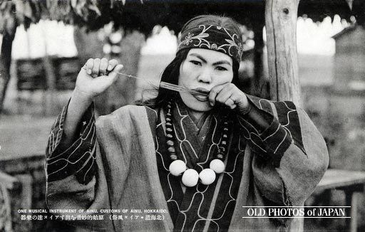 1920's. An Ainu woman playing the Mukkuri (a Jew's harp). The Mukkuri is a traditional Ainu musical instrument played by women. It is made of carefully cut bamboo with two strings, and measures about 10 by 1.5 cm (3.9 by 0.6 inches). The player vibrates the tongue cut out of the bamboo by pulling one of the strings, while holding the instrument in front of the mouth. Volume and tone colors are changed by changing the shape of the mouth.