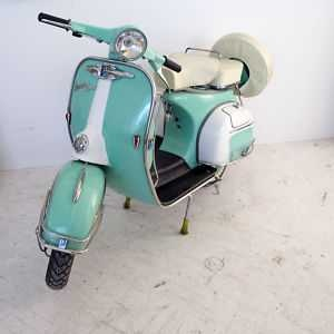 1966 Vespa Sea Foam Scooter -   This scooter is a real beauty, it was love at first sight. Two seater with cream upholstery and spare tire cover. Three white wall tires with matching sea foam and chrome centers.