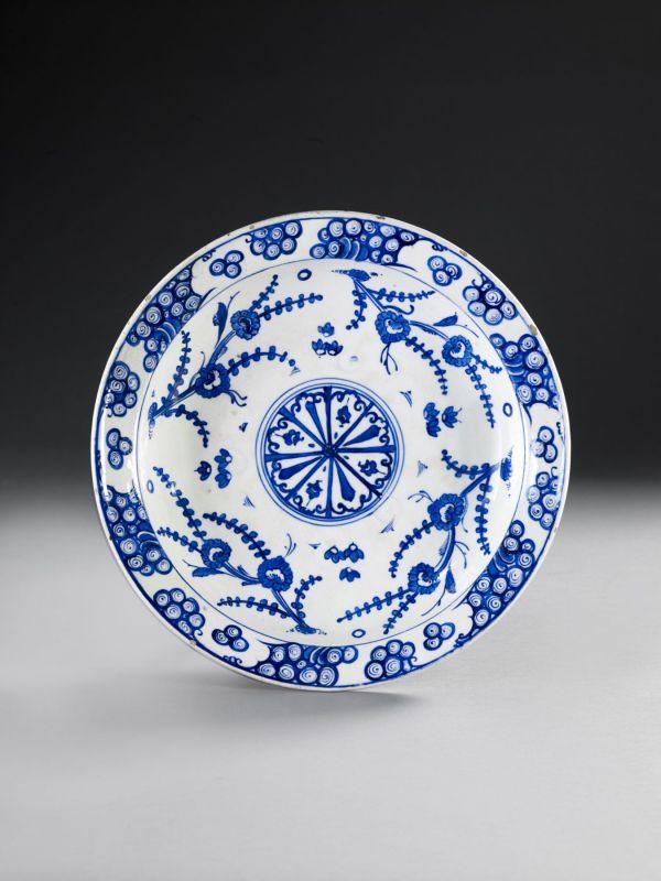 """PLAT BLEU ET BLANC À LA ROSACE, IZNIK, VERS 1570-1575  Grand plat """" tabak """" décoré d'une rosace à huit pétales dans un rondeau qu'entourent quatre rameaux fleuris.  Sur le marli, vagues et rochers. Au revers, douze motifs floraux. Fêle sur le marli. Trous de suspension.  Diamètre : 34 cm. (13 ½ in.)    AN IZNIK BLUE AND WHITE POTTERY DISH PAINTED WITH FOUR FOLIATE STEMS AROUND A ROSETTE, CA.1570-1575"""