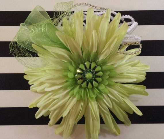 Green fascinator with gold accents. A vibrant and showy piece. Measures 7 by 7. Mounted on a 3.5 by 2 plastic haircomb. Dare to be lovely in lime