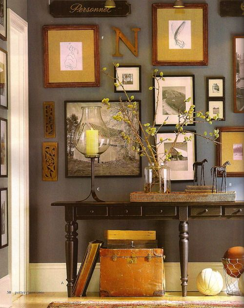 Love the mix match in size and color of the art work against the dark wall & furniture. (Art: mustard, white, black, brick red; Wall: gray; Furniture: chocolate)