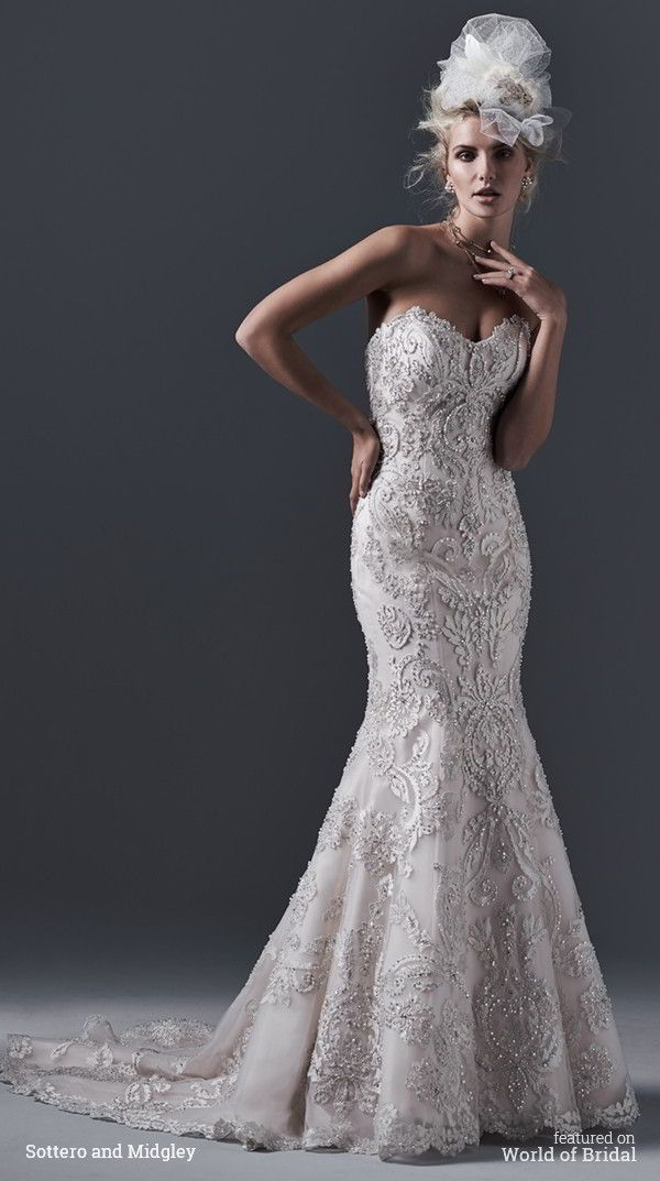 Dramatic lace appliqués on tulle, embellished with dazzling Swarovski crystals and pearls, drift down the length of this fit and flare wedding dress.