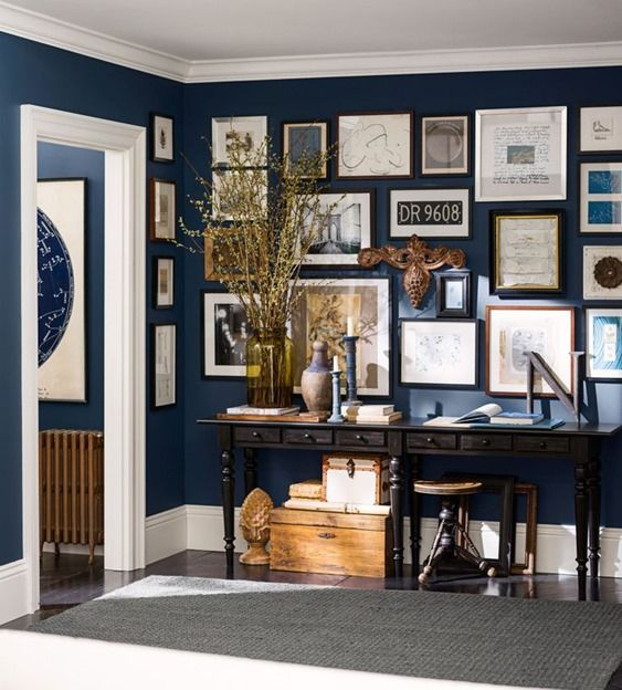 Pottery Barn's partnership with Sherwin Williams led to Naval blue as the backdrop to this well curated wall gallery, it's navy blue perfect...