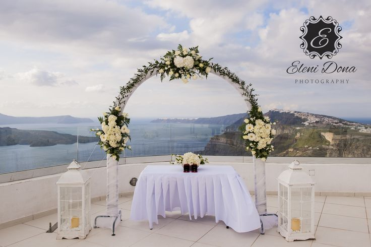Flower decoration with Arch, decorated with roses. This is from Tim  Rachel wedding, in Santo wines, Santorini island. Wedding design  planning by www.weddingingreece.com. Wedding photography by www.elenidona.com #santorini #weddingingreece #santoriniwedding #weddingplannergreece
