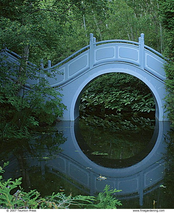A moon bridge was inspired by a similar structure in a ChineseGarden- Les QuatreVents  Gardens ; Quebec, Canada- Via Fine Gardening Magazine