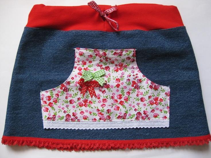 Rokje van een oude spijkerbroek met zakje van een witte stof met roze en rode bloemetjes. Binnenkant zakje is van een rode stof met witte stipjes. Op