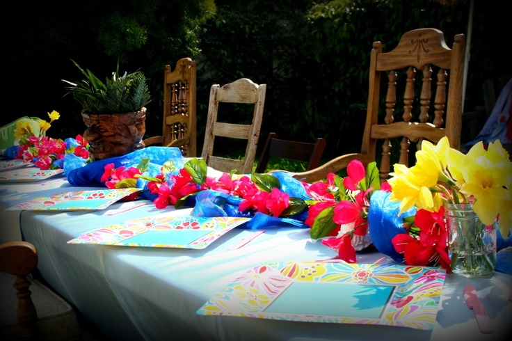 Luau table setting with rustic chairs at kids hawaiian party