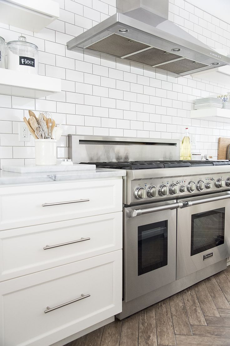 white cabinetry + subway tile + floating shelves