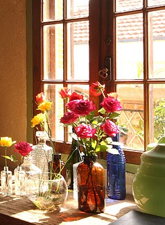 Garrafas simples funcionam como vasos para as flores e dão charme ao móvel sob a janela