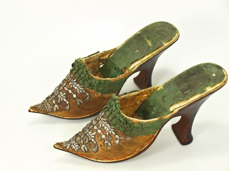 Pair of women's mules, first half 18th century. Orange silk, embroidered with stylized floral motifs in silver metallic thread, green silk ribbon trim, high curved heel, pointed toe.