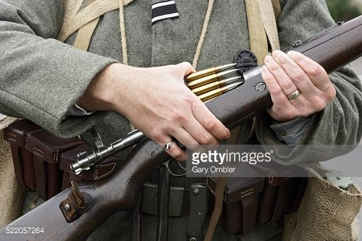 Man wearing World War One Stormtrooper uniform, loading Mauser carbine with five round ammunition clip, mid section