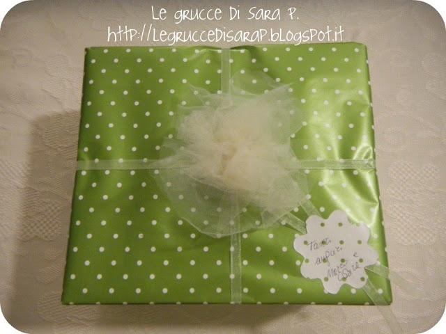Pacco regalo con carta a pois bianchi su sfondo verde. Nastro sottile di organza color avorio e rosa di tulle
