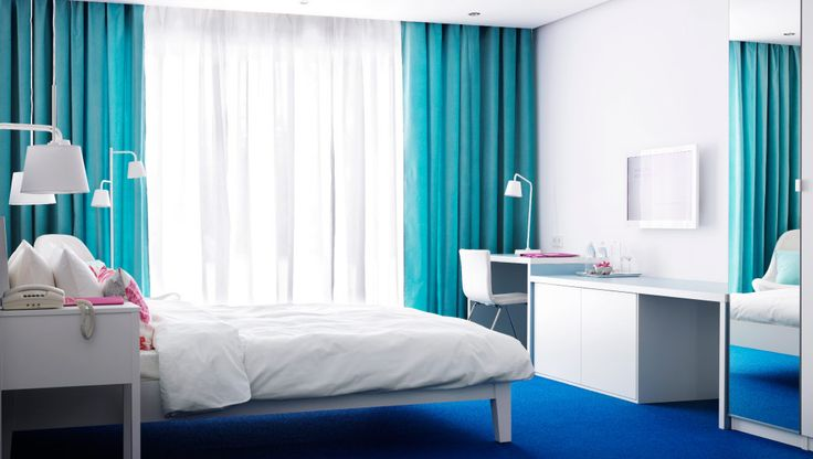 A hotel room with white furniture and turquoise curtains