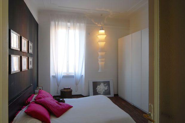 Nella camera da letto il lungo armadio bianco dà risalto all'andamento verticale della lampada da soffitto Falkland di Bruno Munari per Dane...
