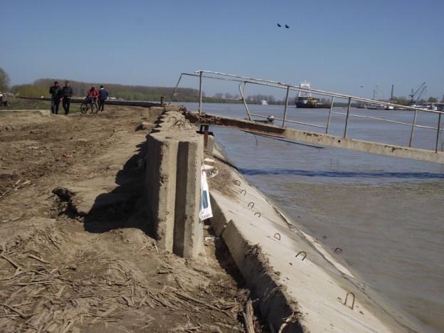 La acest dig se lucrează din 2002, spun cei care locuiesc aici. În 2012 lucrările s-au oprit. Din cauza lipsei banilor, spun autorităţile locale.  În timp ce aproape întreaga localitate de peste Dunăre este protejată de inundaţii, în zona bisericii, chiar la punctul de acostare a navelor care transportă persoane peste Dunăre, câţiva metri au rămas descoperiţi.