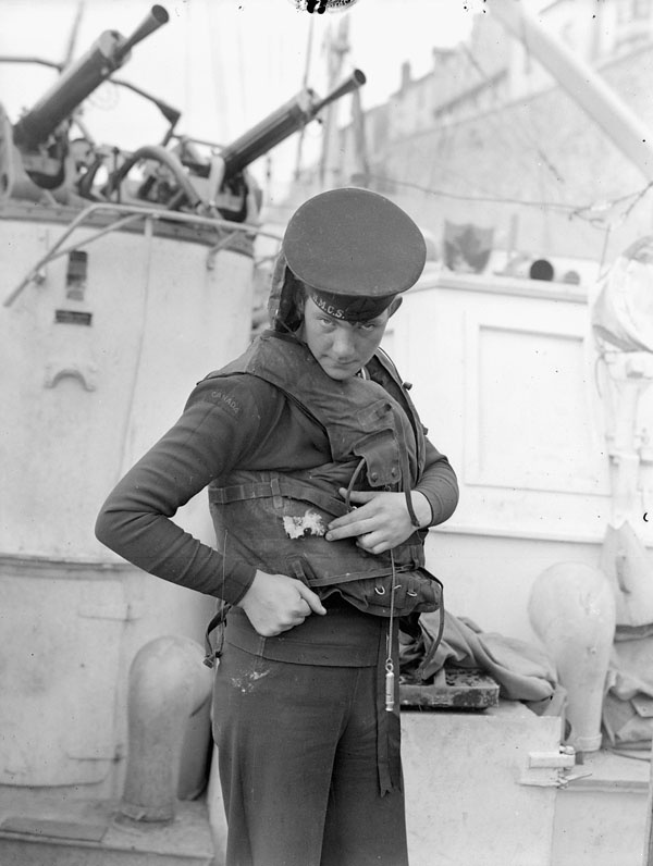 A Canadian sailor of a Motor Torpedo Boat shows off a bullet hole in his life jacket received during action with German escort ships off the coast of France, 1944